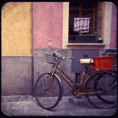 Bike Baskets in Monterosso is an art print of a parked bicycle in Cinque Terre.