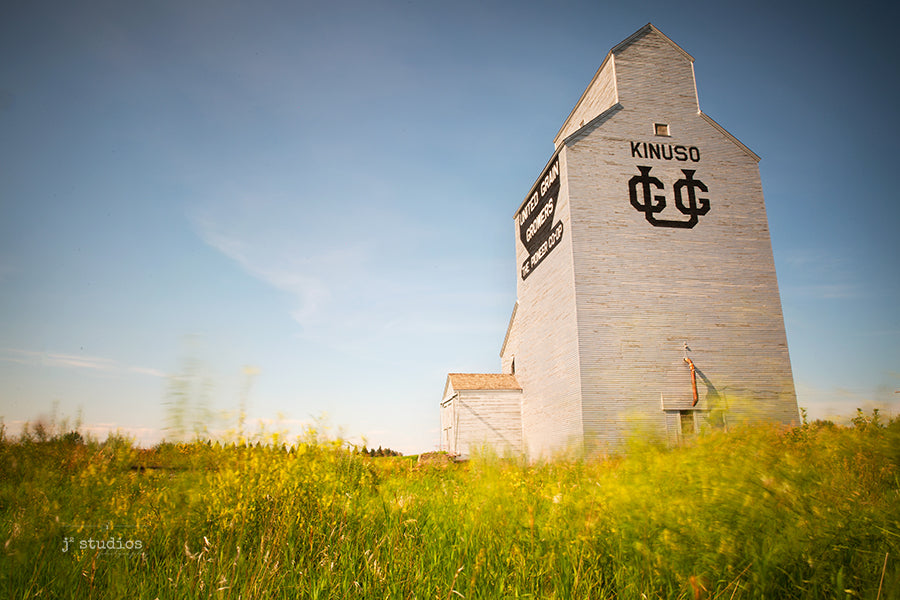 Image of the United Grain Growers Elevator in Kinuso, Alberta looming over a field of blowing wild grass. Prairie stories as told by the songs of the wind.