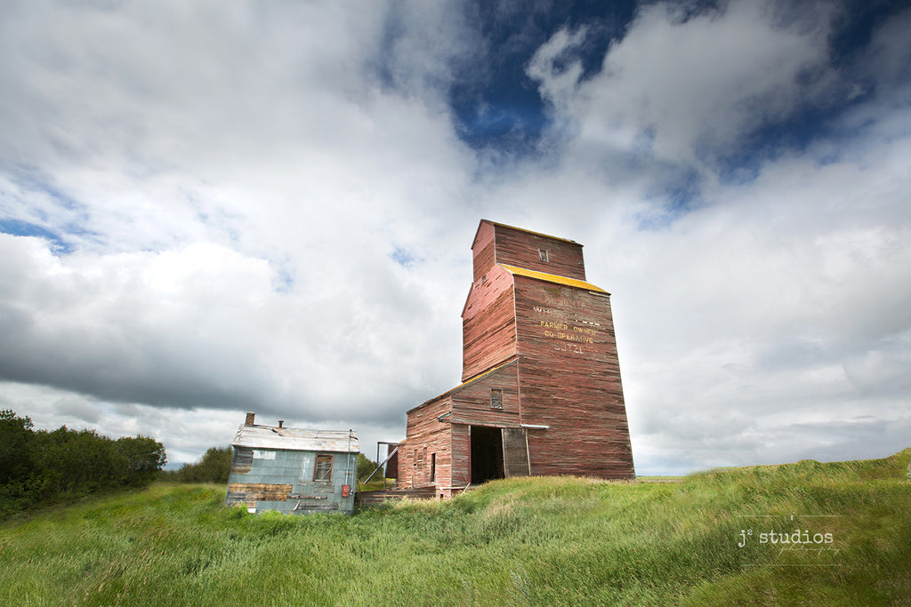 Image of the Butze grain elevator standing tall near Chauvin, Alberta, The weathered Alberta Wheat Pool grainery standing like a beacon on the Canadian Prairies.