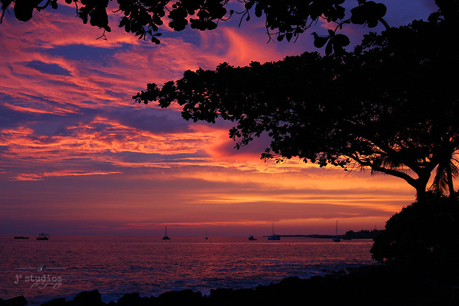 Crimson Skies is an art print of the setting sun over the Pacific Ocean on the Big Island of Hawaii.