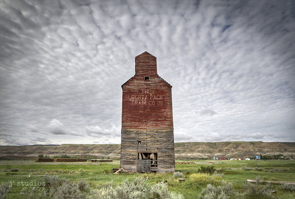 Picture of Alberta Pacific Railway Company grain elevator in Dorothy, Alberta with streaming clouds above. Badlands photography by Larry Jang.