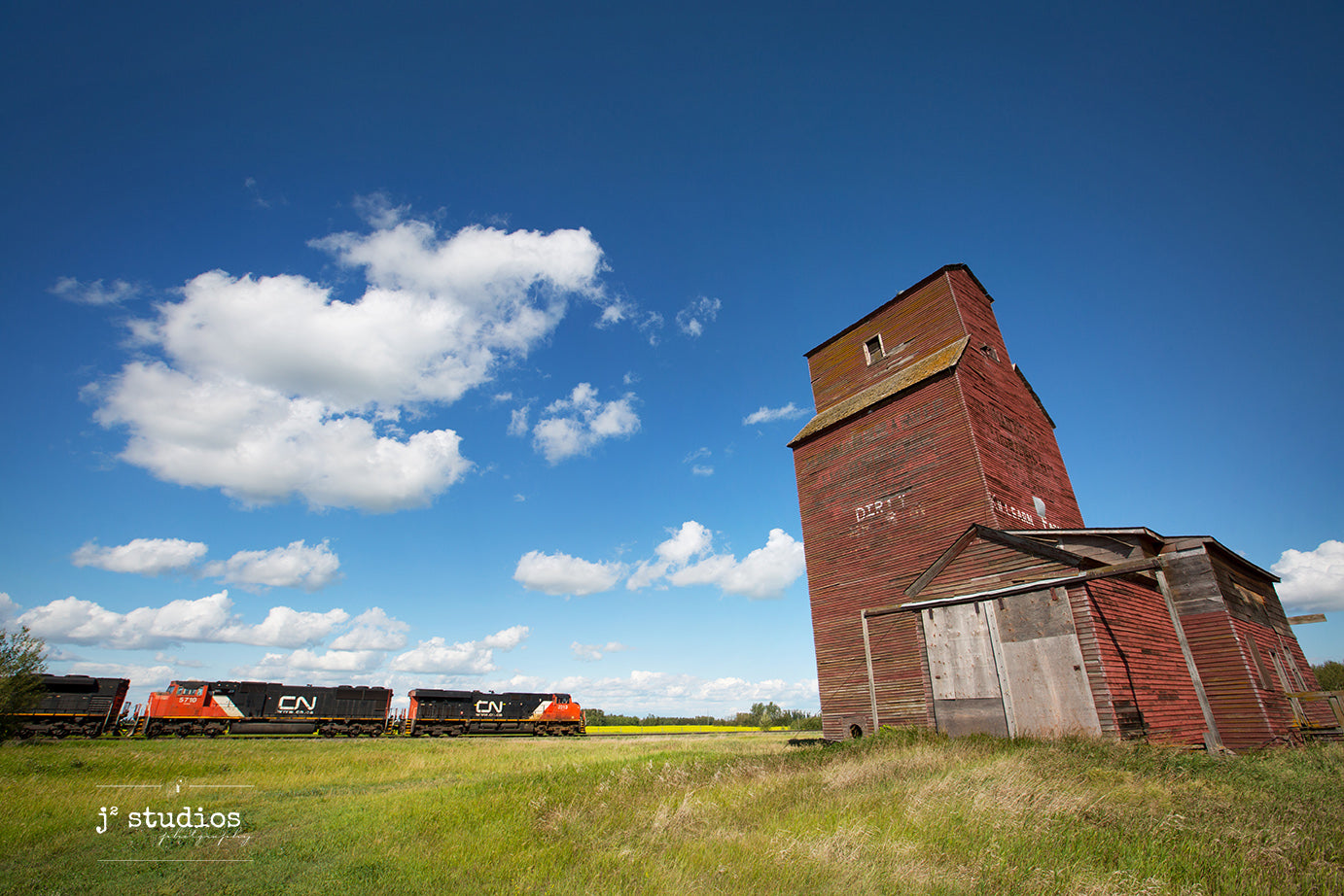 Picture a CN freight train passing Dirty Shorts grain elevator in Shonts, Alberta. Canola field in background. Alberta photography by Larry Jang.