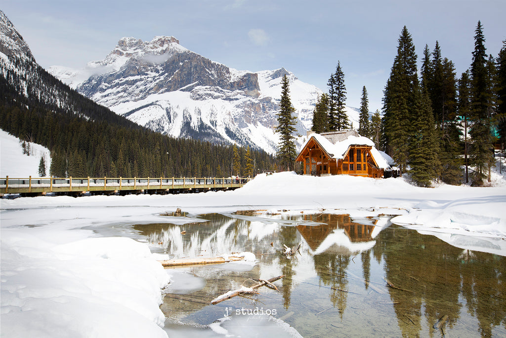Image of the pristine and romantic Emerald Lake Lodge on the frozen shores of Emerald Lake. President's Peak looms in background. Best Canadian Rockies photography by Larry Jang.