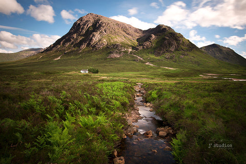 Image of creek with its water flowing peacefully towards an abandoned house by the mountains of Glen Coe in the Scottish Highlands. Landscape Travel Photography J2 Studios.
