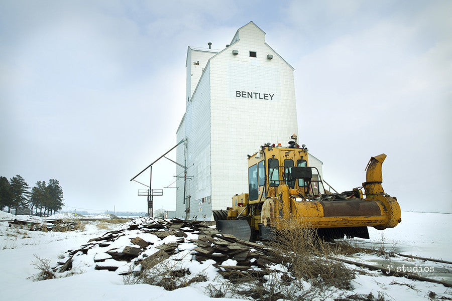 Image of a Railroad Snow Plow parked in front of the Bentley Grain Elevator in Alberta. Art Prints of Alberta.