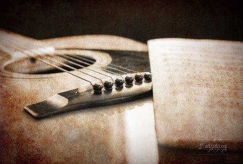 Guitar acoustics is an vintage sepia themed art print of an acoustic guitar and its sheet music.