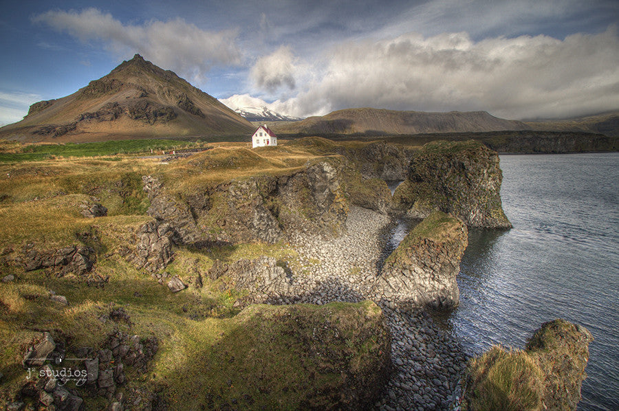 Home By the Sea is an image of a charming oceanfront home nestled along the cliffs of Arnarstapi Village in West Iceland.
