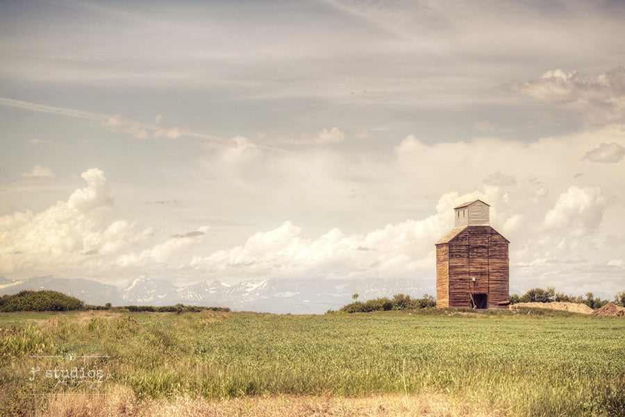 It Stood Weathered Against the Mountains is a sentimental inspired art print of a grain elevator with Glacier National Park in the background. Montana Photography.