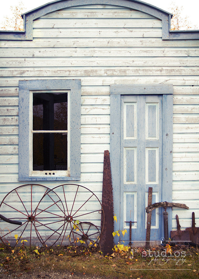 Klondike Blue is an art print of a door and various mining tools in Yukon Territory, Canada.