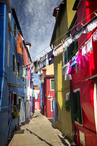 Laundry in Burano is an art print of clothes drying in a colorful alleyway in the charming Italy