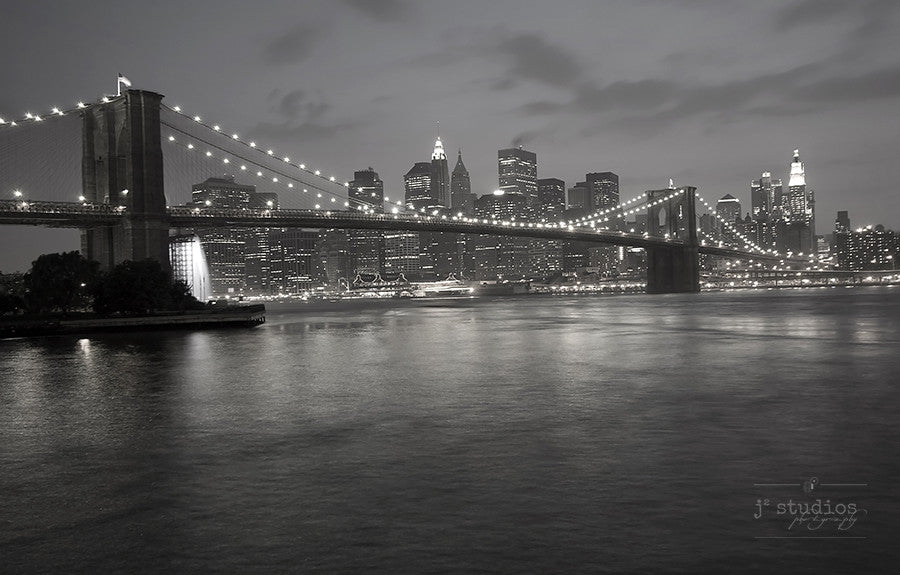 Manhattan at Night is a black and white art print of the iconic New York City skyline and the Brooklyn Bridge.