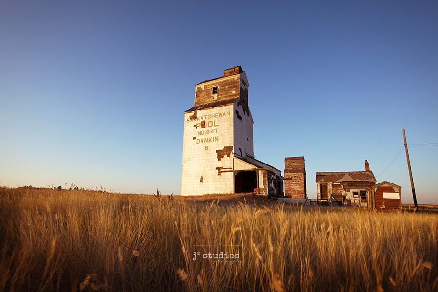 Image of two grain elevators defying the test of time and standing alone on the Saskatchewan Prairies. Heritage themed photography.