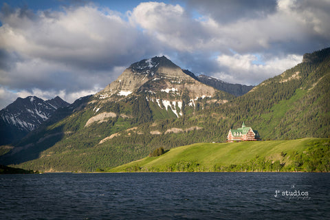 Image of the Prince of Wales Hotel standing peacefully along the shores of Upper Waterton Lakes in Waterton National Park in Alberta, Canada.  Iconic historical hotel in the pristine Canadian Rockies. Alberta Photography.