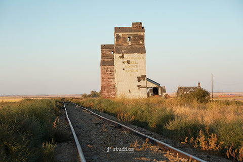 Image of a pair of grain elevators standing steadfast along the Saskatchewan railroad tracks. Prairies Photography.