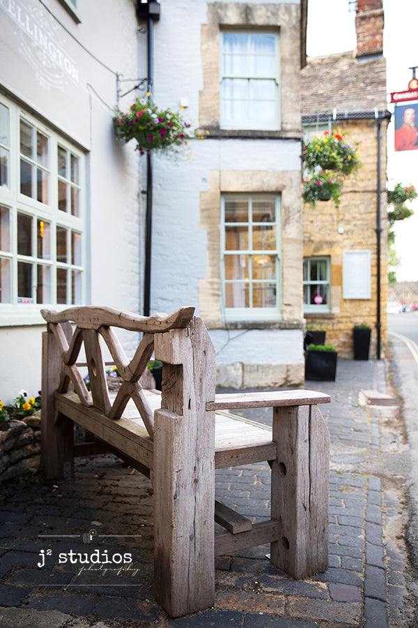 Art print of a charming wooden park bench in a Cotswolds village in Gloucestershire, England. Travel photography.