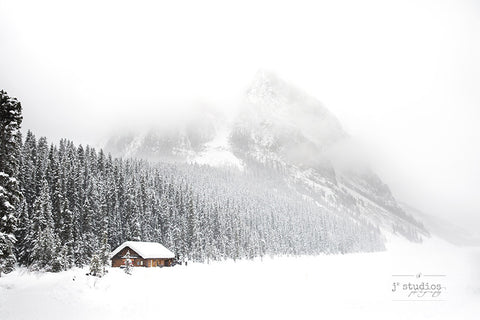 Snowy Day in Louise is a winter wonderland themed image of a Log Cabin and Mount Fairview in Banff National Park. Winter Landscape. Rocky Mountain Photography.