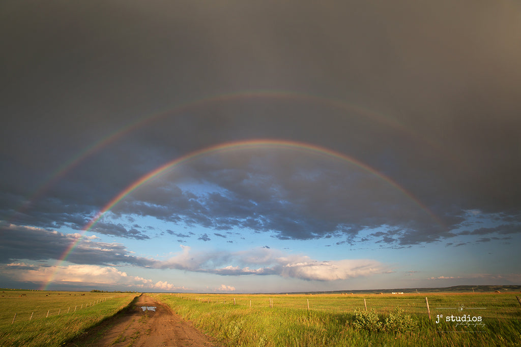 Beautiful image of a double rainbow arcing over an inviting country road and a farmers field filled with bales of hay. Canadian Photography.