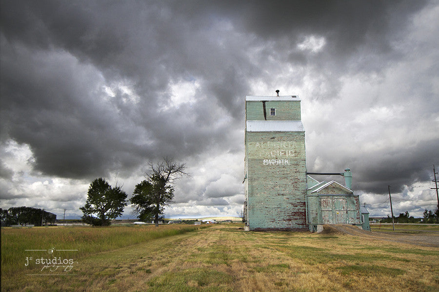 Art print of an approaching storm by the grain elevator in Magrath, Alberta. Canadian Prairies photography.