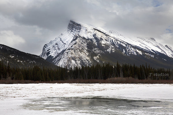 Image of Rundle Mountain in Banff National Park looming over a frozen lake. Canadian Winter Paradise.