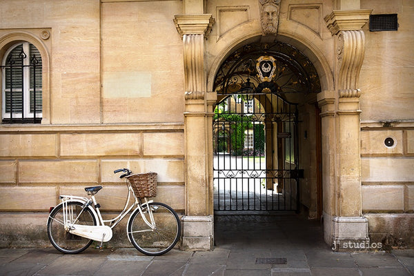 European themed image of a white ladies bicycle parked against the wall at Cambridge University in UK. Bike photography.