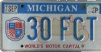 MI-104 Michigan Worlds Motor Capital License Plate light blue numbers on white with antique car