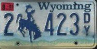 Wyoming License Plate blue numbers and bucking bronco on sky and mountains