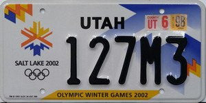 Utah Olympic Winter Games 2002 State License Plate black numbers on white with blue orange yellow snow flakes and Olympic logo