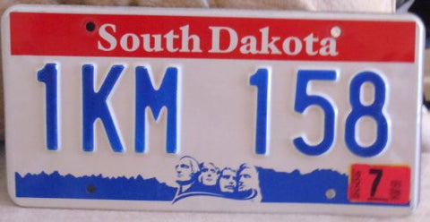 South Dakota red white and blue license plate with blue numbers from around 2005 with the four faces on bottom of the plate