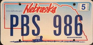 Nebraska License Plate blue numbers on sunset with Covered Wagon flat non-embossed
