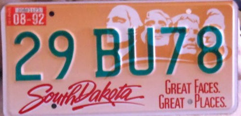 South dakota great faces, great places license plate gold and white back ground with green numbers with a picture of the four faces in the back ground