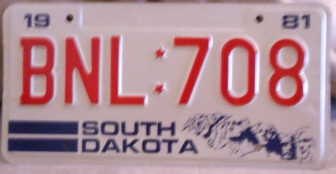 South Dakota 1981 State License Plate Red,white and Blue with Red Numbers and Four Faces on the Lower Right Hand Corner