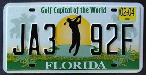 Florida Golf Capital of the World license plate black numbers on green golf course with golfer against sunrise