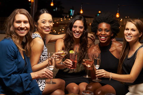 Group of women happily drinking
