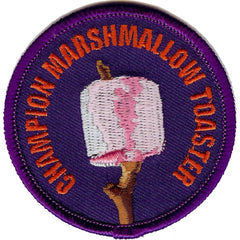 Embroidered Badge with an image of a Marshmallow on a stick and the words 'Champion Marshmallow Toaster'