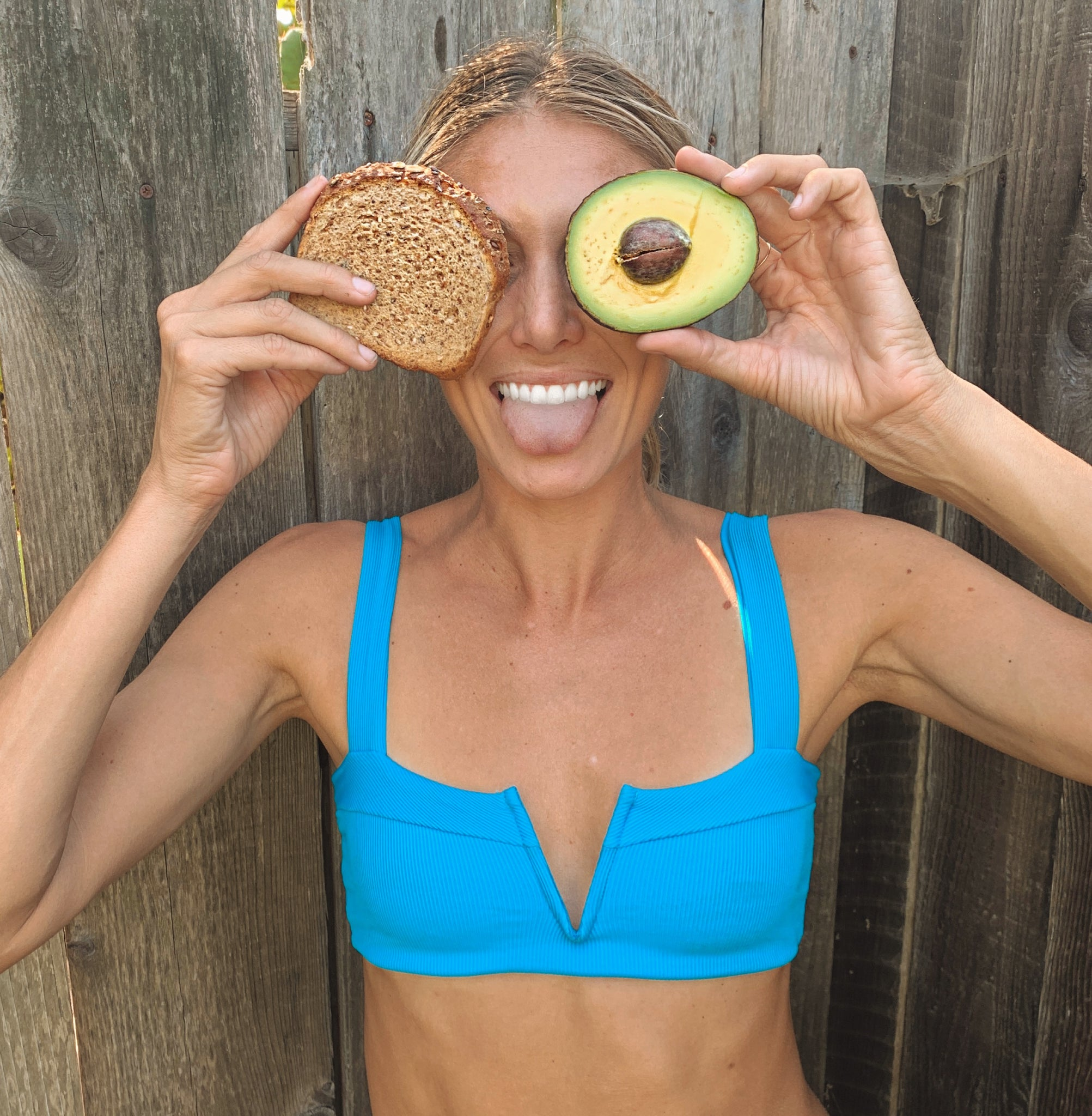 Fitness trainer McKenna Waitley wearing L*Space swim and holding an avocado and a piece of toast