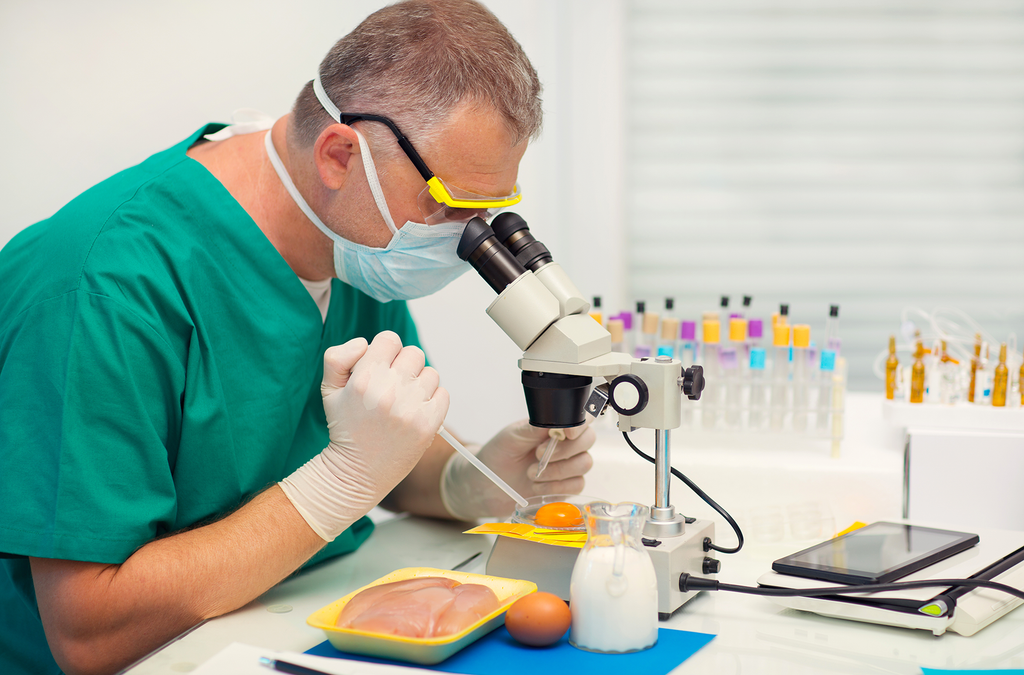 scientist analysing food specimens under a microscope