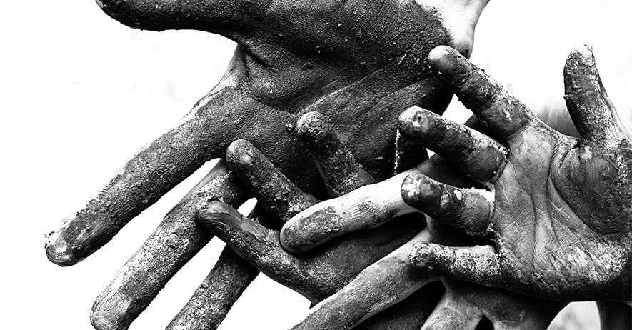Adult and children's hands covered in mud