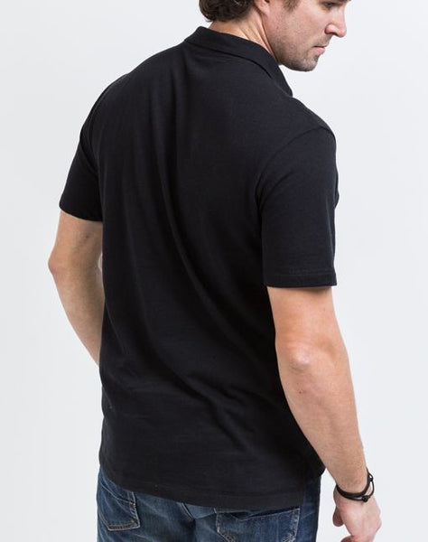The back view of the Alex golf polo in black is known for its structure and good fit.