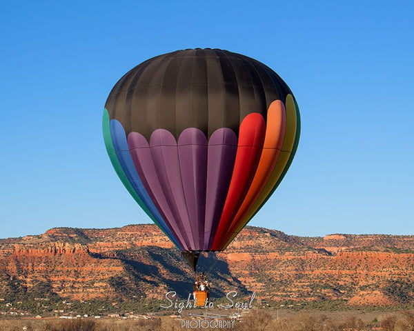 Hot air balloon over red cliffs of the southwest.