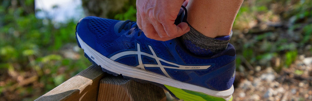 tying laces of blue running shoe before fartlek training
