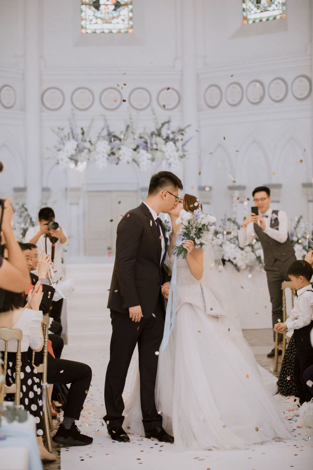 Bride and groom sharing a first kiss with a personal bridal bouquet in the bride's hand