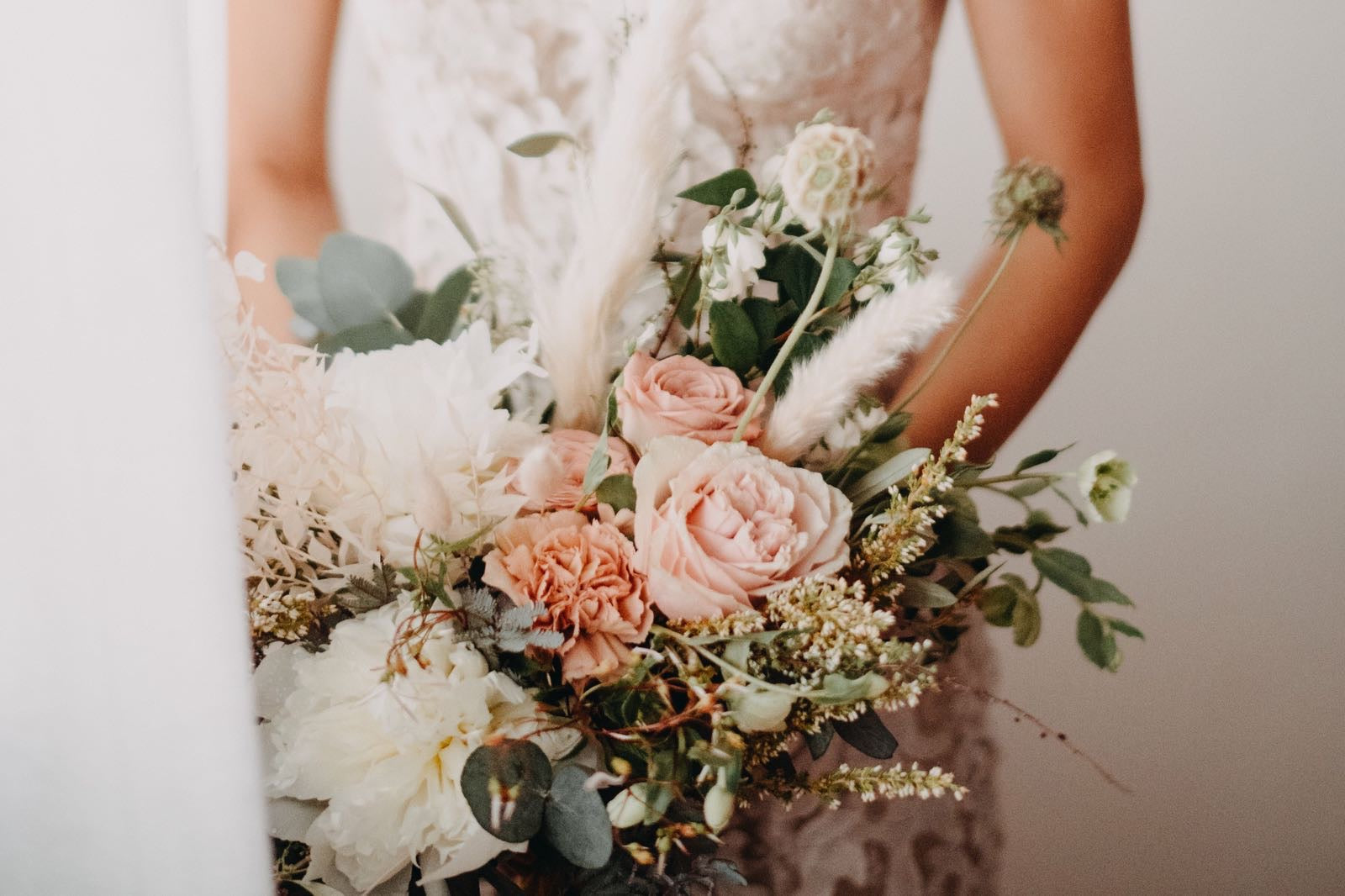 Bride personal bouquet arrangement of pink and white peonies, wax flowers, rabbit's tail