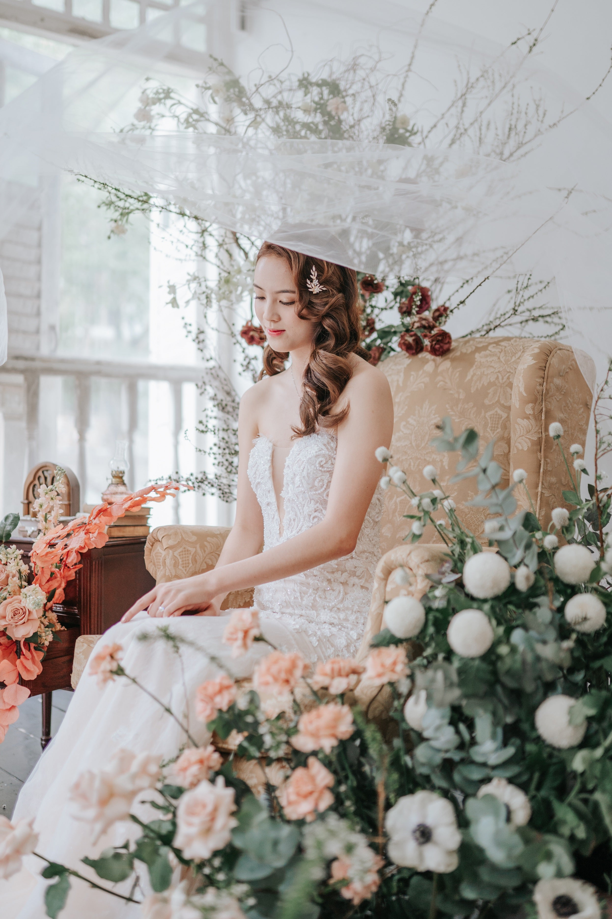 Bride sitting in a gold armchair surrounded by flowers. Wedding veil drifting abovehead
