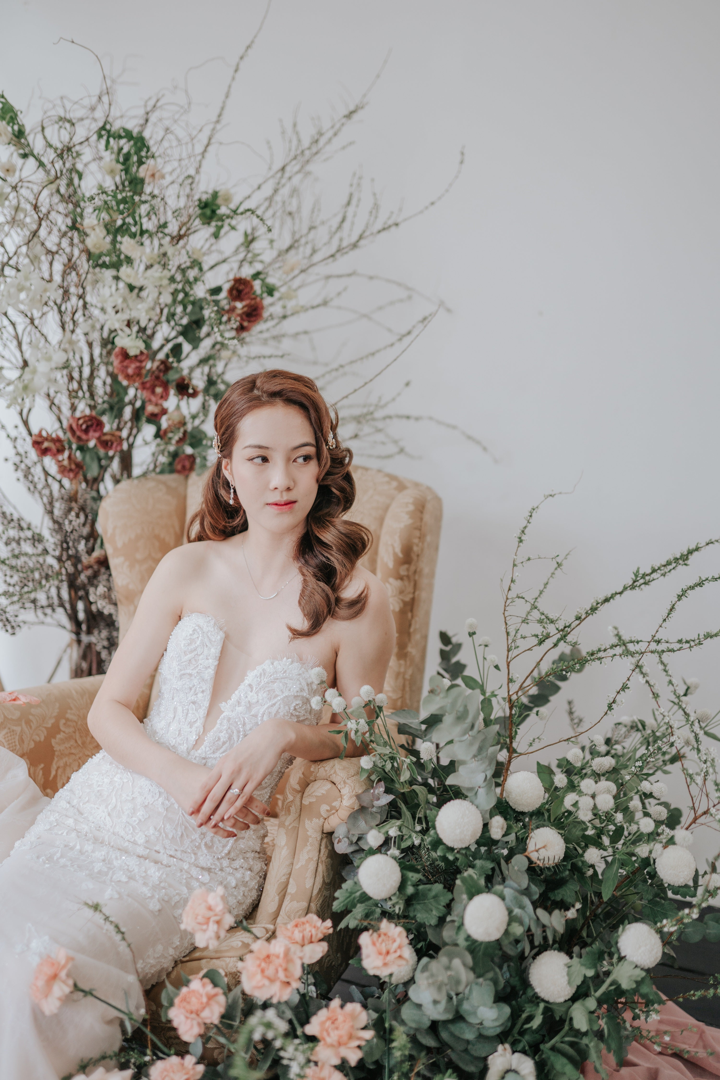 Bride wearing deep-V, strapless wedding dress with a diamond wedding ring, seated looking sideways