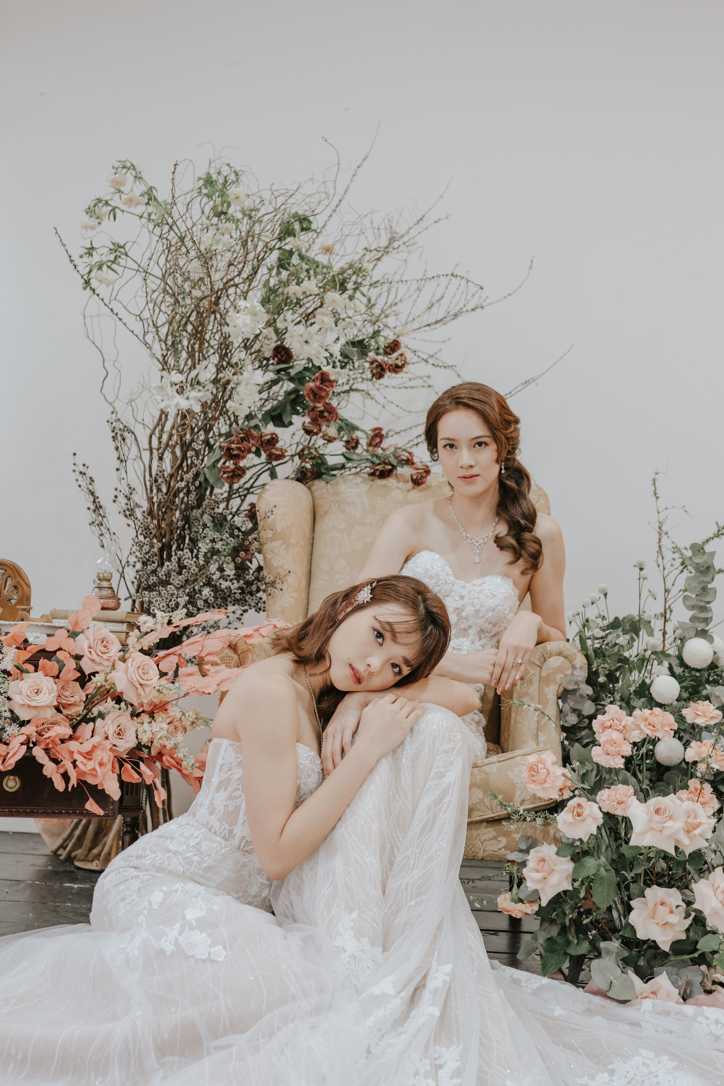 2 brides in wedding dresses by Blush House Bridal, seated, surrounded by flowers
