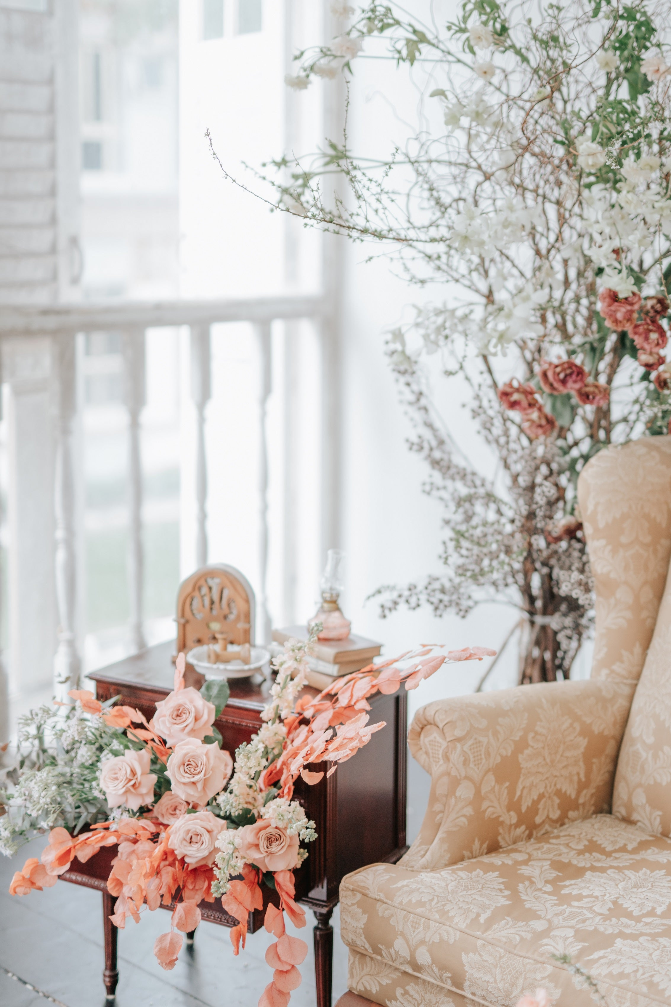 Orange flowers and roses styled in a brown bedside table drawer next to a gold armchair