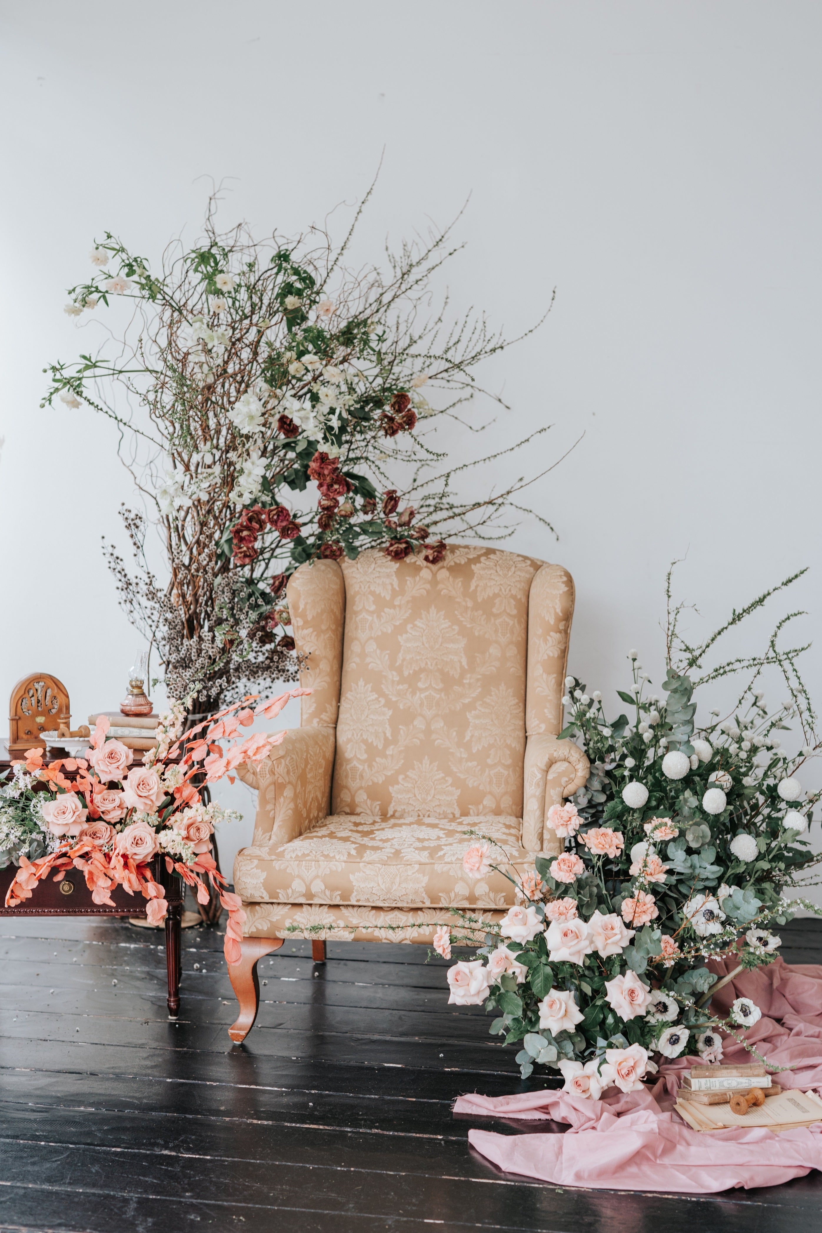 Gold vintage armchair surrounded by flower installation. Pink drapes styled on the floor