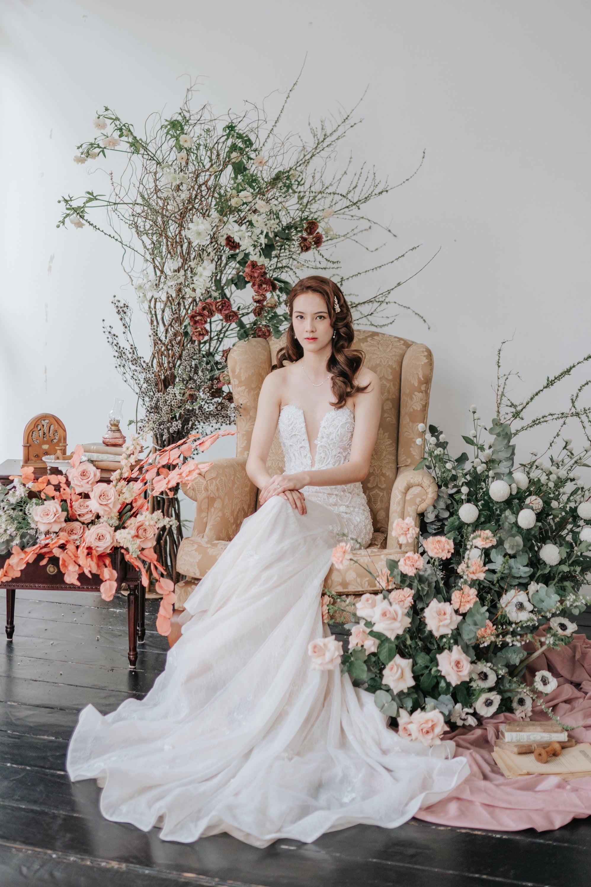 Bride in strapless, ivory wedding gown sitting on a gold armchair surrounded by styled flowers