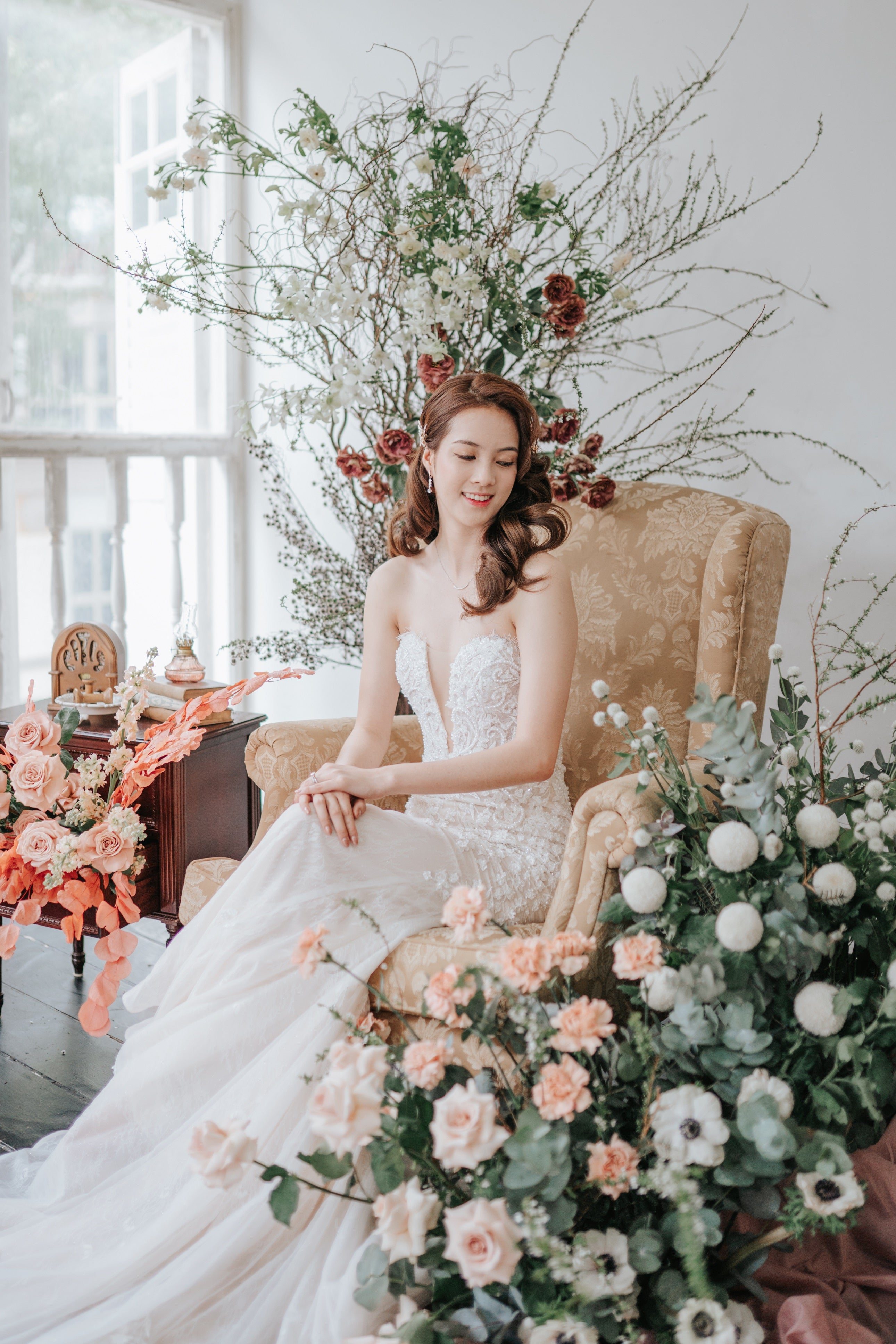 Bride sitting on an armchair surrounded by arranged brambles and flower installations with mainly eucalyptus