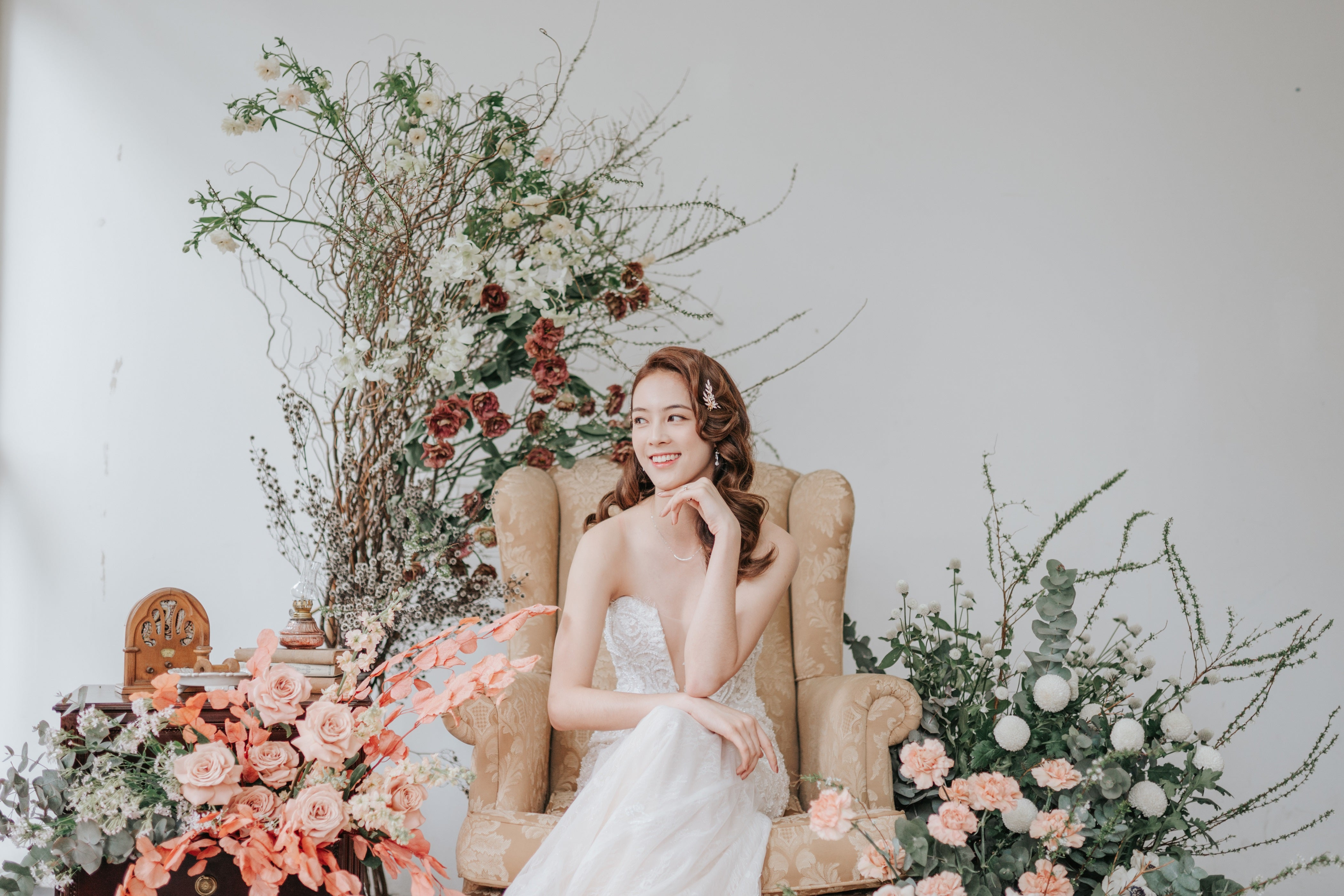 Bride looking sideways, smiling, seated on gold armchair surrounded by arranged flower installation